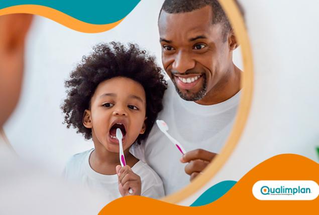 adulto e criança fazendo a higiene bucal